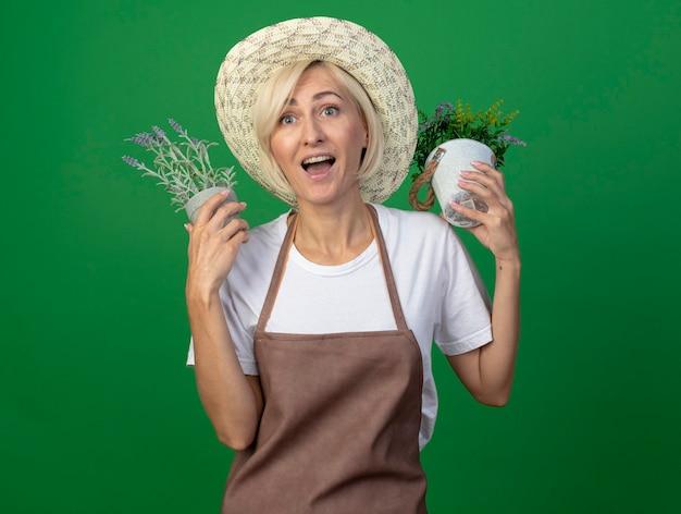 Pod wrażeniem blond ogrodniczka w średnim wieku w mundurze, w kapeluszu, trzymająca doniczki w pobliżu głowy, patrząc na bok odizolowany na zielonej ścianie