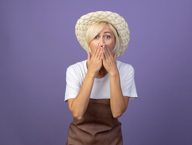Pod wrażeniem blond ogrodniczka w średnim wieku w mundurze w kapeluszu, trzymająca ręce na ustach, odizolowana na fioletowej ścianie z miejscem na kopię
