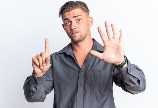 Pod wrażeniem blond przystojny mężczyzna gestykuluje sześć palcami