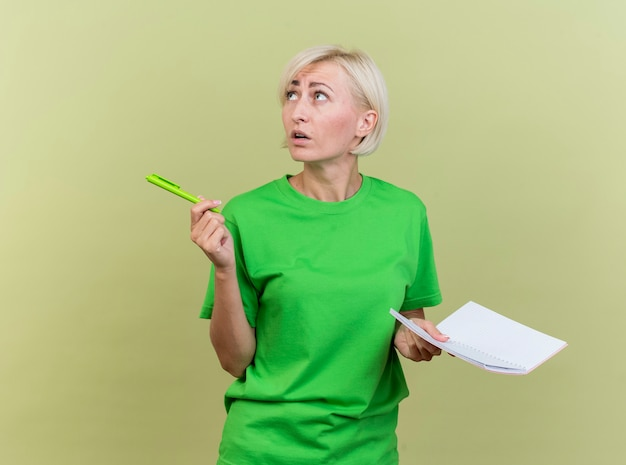 Pod wrażeniem blondynki kobieta w średnim wieku, trzymając pióro i notes, patrząc na bok na białym tle na oliwkowej ścianie