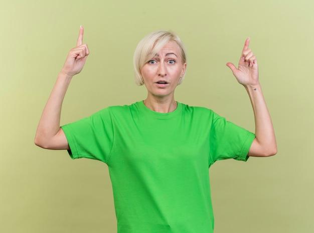 Pod wrażeniem blondynki słowiańska kobieta w średnim wieku patrząc na kamery skierowaną w górę na białym tle na oliwkowym tle