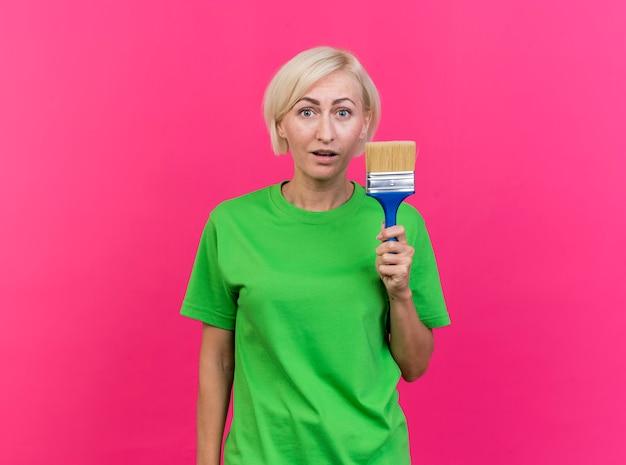 Pod wrażeniem blondynki słowiańska kobieta w średnim wieku patrząc na kamery trzymając pędzel na białym tle na szkarłatnym tle z miejsca na kopię
