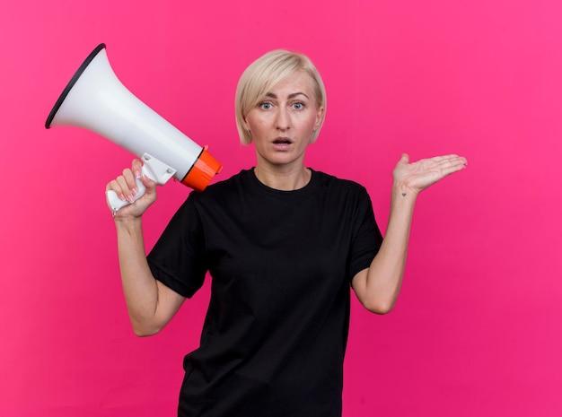 Pod wrażeniem blondynki słowiańska kobieta w średnim wieku patrząc na przedni głośnik pokazujący pustą dłoń odizolowaną na różowej ścianie