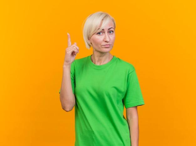 Pod wrażeniem blondynki słowiańska kobieta w średnim wieku patrząc na przód skierowaną w górę na białym tle na żółtej ścianie z miejsca na kopię