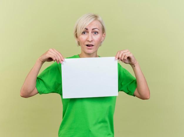 Pod wrażeniem blondynki słowiańska kobieta w średnim wieku trzymając czysty papier patrząc z przodu na białym tle na oliwkowej ścianie