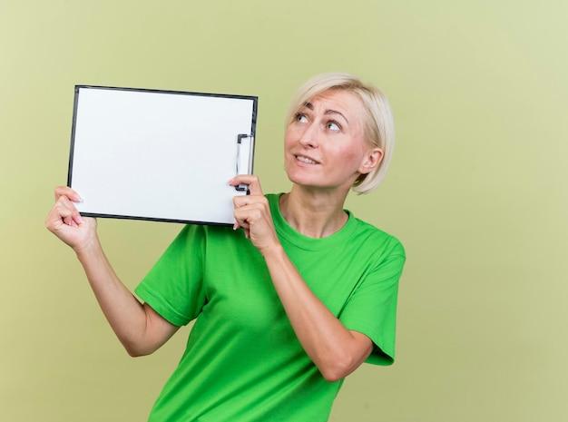 Pod wrażeniem blondynki słowiańska kobieta w średnim wieku, trzymając schowek w pobliżu głowy, patrząc z boku na białym tle na oliwkowej ścianie z miejsca na kopię