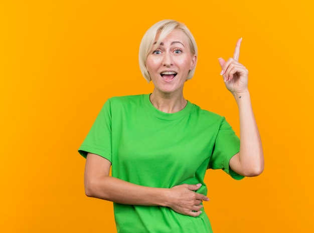 Pod wrażeniem blondynki w średnim wieku kobieta patrząc z przodu skierowaną w górę na białym tle na żółtej ścianie