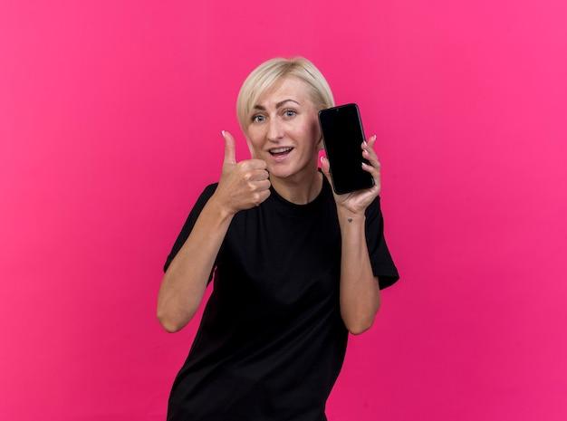 Pod wrażeniem blondynki w średnim wieku kobieta pokazuje telefon komórkowy i kciuk patrząc na przód na białym tle na różowej ścianie