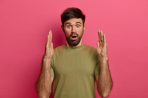 Pod wrażeniem brodaty mężczyzna kształtuje duży przedmiot, mówi o wielkości prezentowanego pudełka