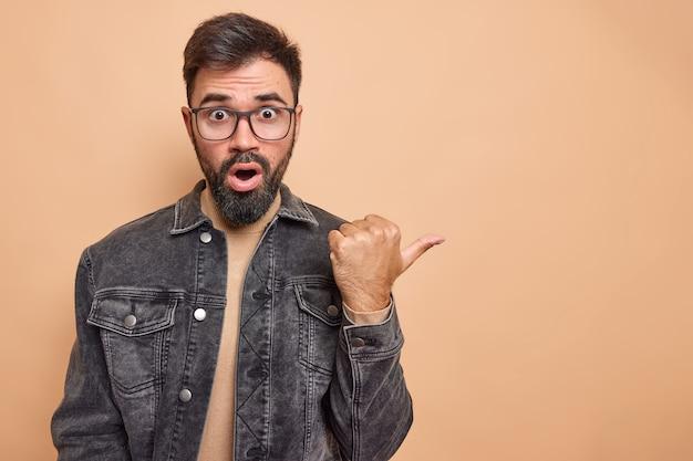 Pod wrażeniem, brodaty, przystojny mężczyzna wskazuje kciukiem!