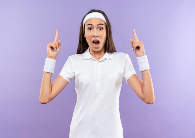 Pod wrażeniem całkiem wysportowanej dziewczyny noszącej opaskę i opaskę skierowaną w górę, odizolowaną na fioletowej ścianie