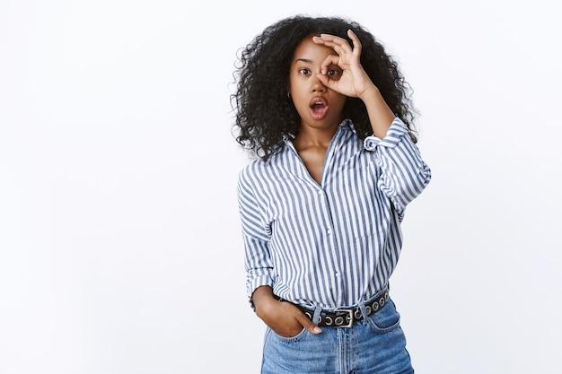 Pod wrażeniem charyzmatyczna zdumiona atrakcyjna nowoczesna afrykańsko-amerykańska pracownica opadająca szczęka otwarta zdumiona, ciekawa patrząca przez ok. ok gest przytłoczony, biała ściana widząc fajną promocję