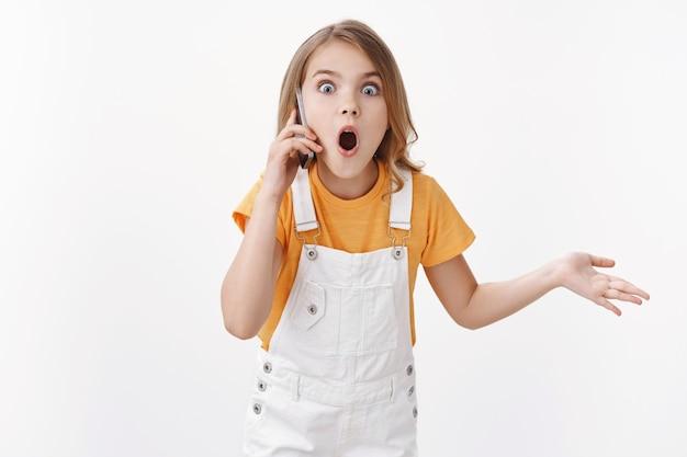 Pod wrażeniem charyzmatycznej blondynki, dziecka rozmawiającego przez telefon, dzwoniącego do przyjaciela plotkującego, gapiącego się zszokowanego i zdumionego otwartymi ustami, gestykulującego podniesioną dłonią wypytywaną, używaj smartfona i opowiadaj soczyste plotki