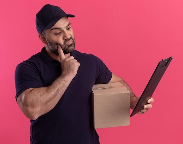 Pod wrażeniem doręczyciel w średnim wieku w mundurze i czapce, trzymając pudełko i patrząc na schowek w dłoni, kładąc palec na policzku odizolowanym na różowej ścianie