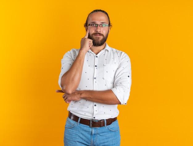 Pod wrażeniem dorosłego, przystojnego mężczyzny w okularach trzymających rękę na brodzie