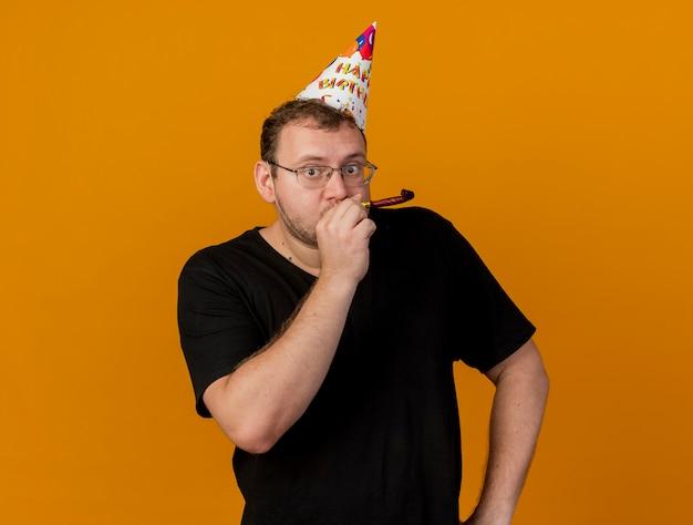 Pod wrażeniem dorosłego słowiańskiego mężczyzny w okularach optycznych w czapce urodzinowej dmuchającej w gwizdek