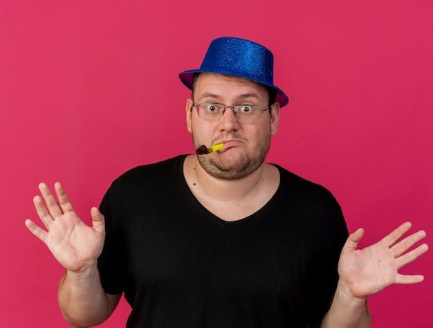 Pod wrażeniem dorosłego słowiańskiego mężczyzny w okularach optycznych w niebieskim kapeluszu imprezowym stoi z podniesionymi rękami, dmuchając w gwizdek imprezowy