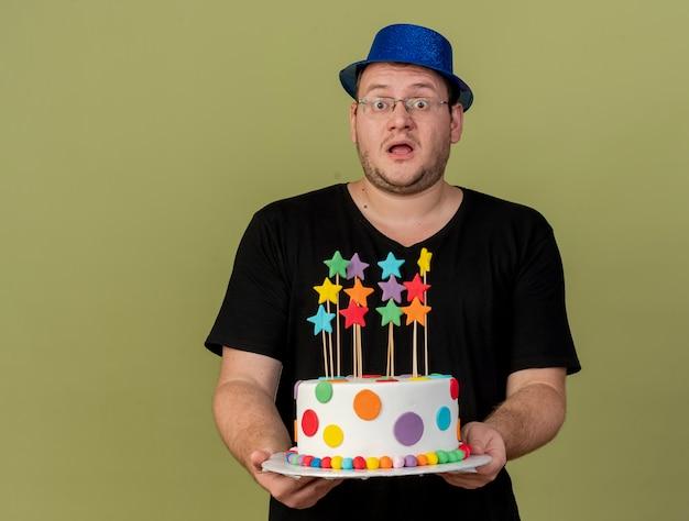 Pod wrażeniem dorosłego słowiańskiego mężczyzny w okularach optycznych w niebieskim kapeluszu imprezowym trzyma tort urodzinowy