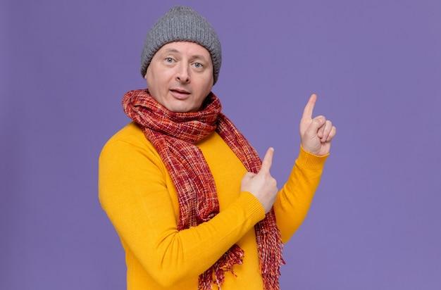 Pod wrażeniem dorosłego słowiańskiego mężczyzny z zimową czapką i szalikiem na szyi skierowanymi do góry