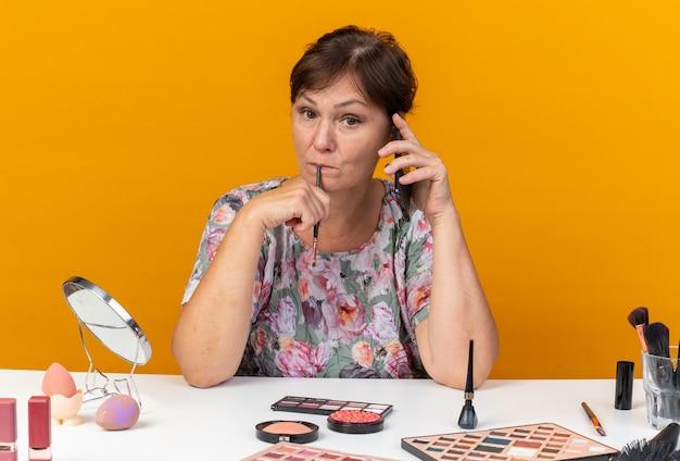 Pod wrażeniem dorosłej kobiety rasy kaukaskiej siedzącej przy stole z narzędziami do makijażu rozmawiającej przez telefon i trzymającej pędzel do makijażu izolowane na pomarańczowej ścianie z miejscem na kopię