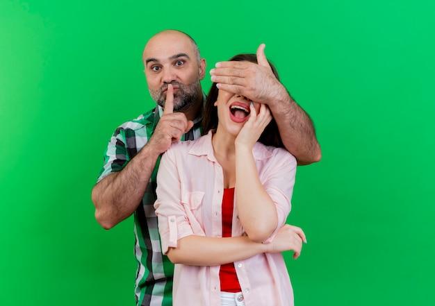 Pod wrażeniem dorosłej pary mężczyzna zakrywający oczy kobiety ręką gestykulującą ciszę kobieta kładąca dłoń na twarzy odizolowana na zielonej ścianie z przestrzenią do kopiowania