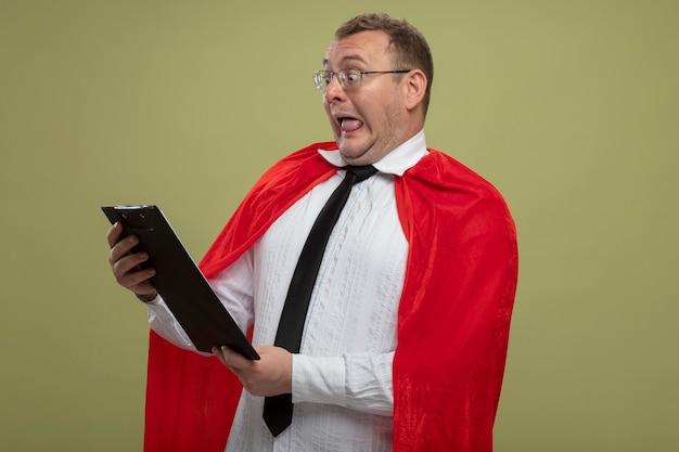 Pod wrażeniem dorosły człowiek superbohatera w czerwonej pelerynie w okularach i krawacie, trzymając i patrząc na schowek na białym tle na oliwkowej ścianie
