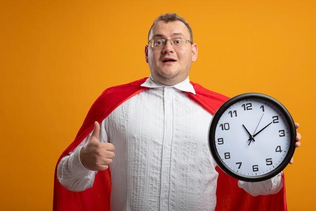 Pod wrażeniem dorosły człowiek superbohatera w czerwonej pelerynie w okularach patrząc na przód trzymając zegar pokazujący kciuk w górę na białym tle na pomarańczowej ścianie