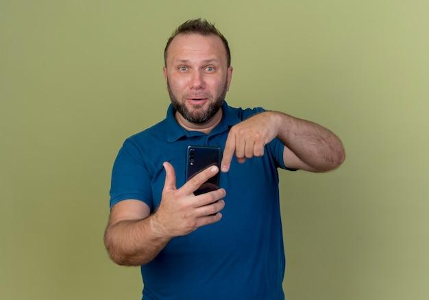 Pod wrażeniem dorosły mężczyzna słowiański gospodarstwa i wskazując na telefon komórkowy patrząc