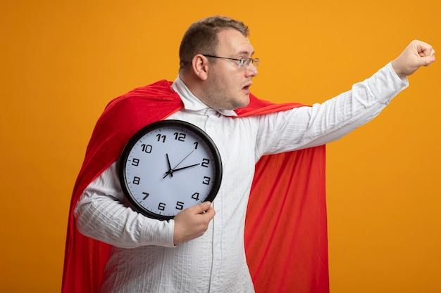Pod wrażeniem dorosły mężczyzna superbohatera w czerwonej pelerynie w okularach trzyma zegar wyciągając pięść patrząc na bok na białym tle na pomarańczowej ścianie