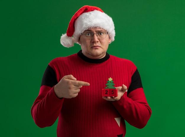 Pod wrażeniem dorosły mężczyzna w okularach i santa hat trzyma i wskazuje na choinkę zabawki z datą patrząc na kamery na białym tle na zielonym tle