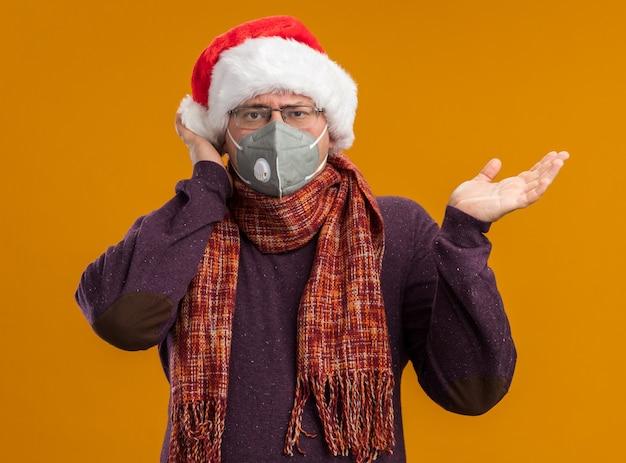 Pod wrażeniem dorosły mężczyzna w okularach ochronnych i czapce świętego mikołaja z szalikiem na szyi patrząc na kamerę pokazującą pustą rękę dotykającą głowy odizolowaną na pomarańczowym tle