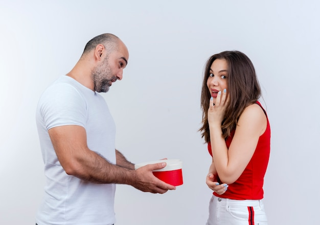 Pod wrażeniem dorosły para mężczyzna trzyma pudełko w kształcie serca patrząc na kobietę i kobietę, dotykając twarzy i patrząc na białym tle