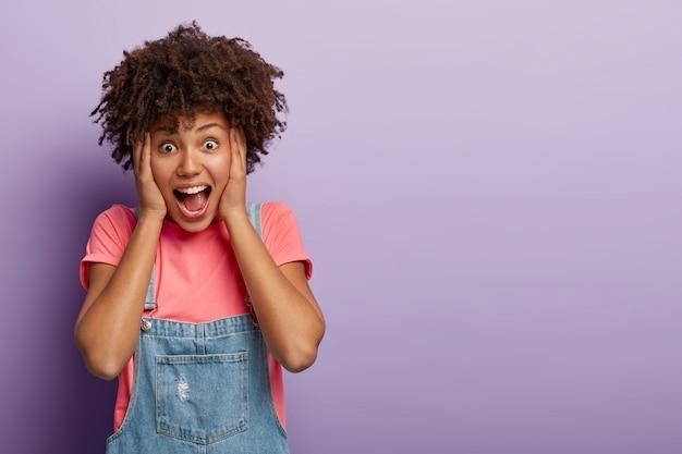 Pod wrażeniem emocjonalna kobieta patrzy z przerażeniem, krzyczy i ma szeroko otwarte usta