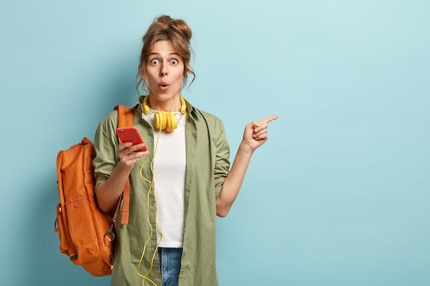 Pod wrażeniem europejska młoda modelka przeszukuje pliki multimedialne w telefonie komórkowym, używa słuchawek stereo do słuchania muzyki, przegląda internet i czatuje, wskazuje zszokowana, nosi modne ubrania
