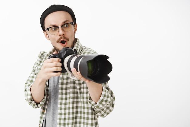 Pod wrażeniem i podekscytowaniem uroczy męski fotograf pracujący nad nowym projektem, trzymając aparat otwierający usta w dźwięku wow, wpatrując się podekscytowany i rozbawiony, widząc niesamowity pomysł na zdjęcie