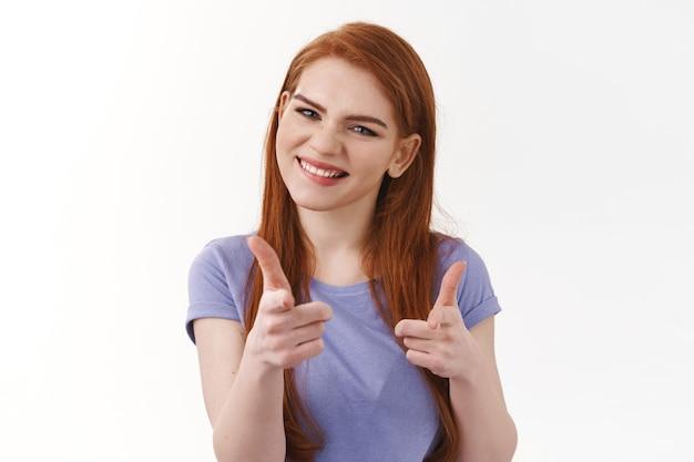 Pod wrażeniem i zadowolona ładna rudowłosa kobieta, pistolety na palce wskazujące i uśmiechnięta zdumiona, gratuluję przyjacielowi dobrze zrobionego, chwalę dobry wysiłek, biała ściana
