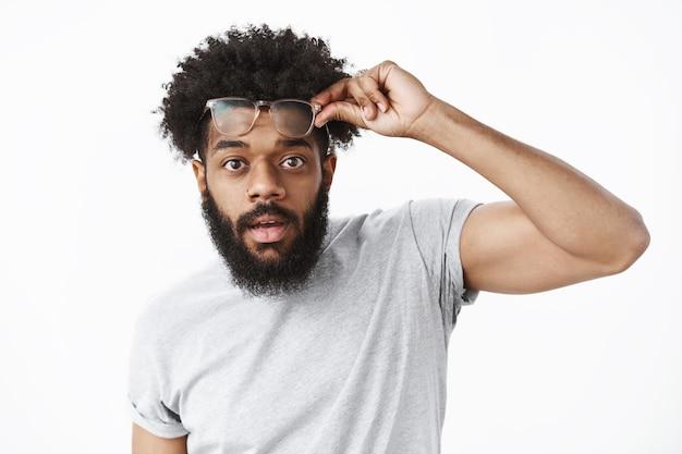 Pod wrażeniem i zdziwieniem przystojny afroamerykanin zdejmujący okulary, oczarowany urodą, trzymający okulary na czole, z otwartymi ustami ze zdumienia, wpatrujący się w kamerę nad szarą ścianą