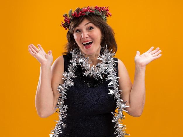 Pod wrażeniem kobieta w średnim wieku ubrana w świąteczny wieniec na głowę i świecącą girlandę na szyi, pokazująca puste dłonie odizolowane na pomarańczowej ścianie