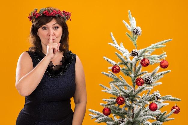 Pod wrażeniem kobieta w średnim wieku ubrana w świąteczny wieniec na głowę i świecącą girlandę na szyi, stojąca w pobliżu udekorowanej choinki