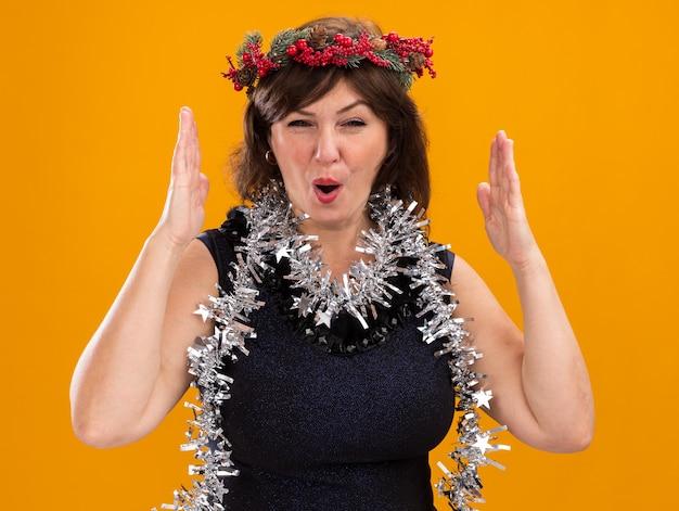 Pod wrażeniem kobieta w średnim wieku ubrana w świąteczny wieniec na głowę i świecącą girlandę wokół szyi robi gest wielkości na pomarańczowej ścianie