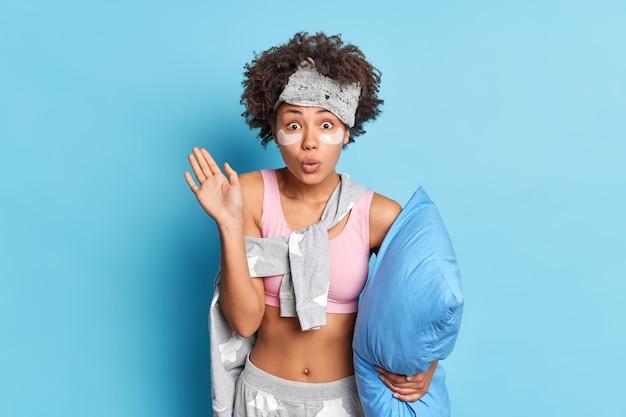 Pod wrażeniem kręcone włosy kobiety wyglądają z zadziwiającym wyrazem twarzy zaskakująco z przodu trzyma rękę uniesioną w pozach piżamy z poduszką odizolowaną od niebieskiego wal