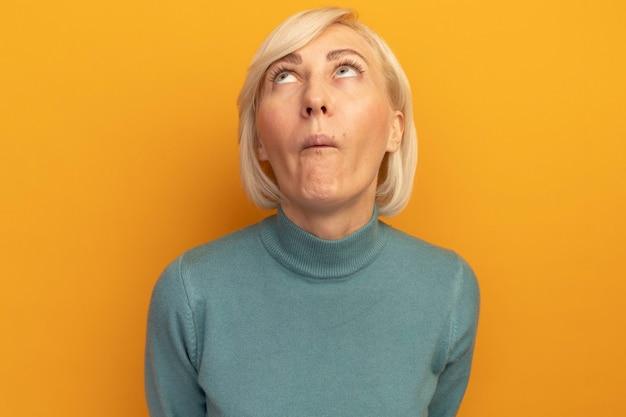 Pod wrażeniem ładna blondynka słowiańska kobieta patrzy w górę na białym tle na pomarańczowej ścianie