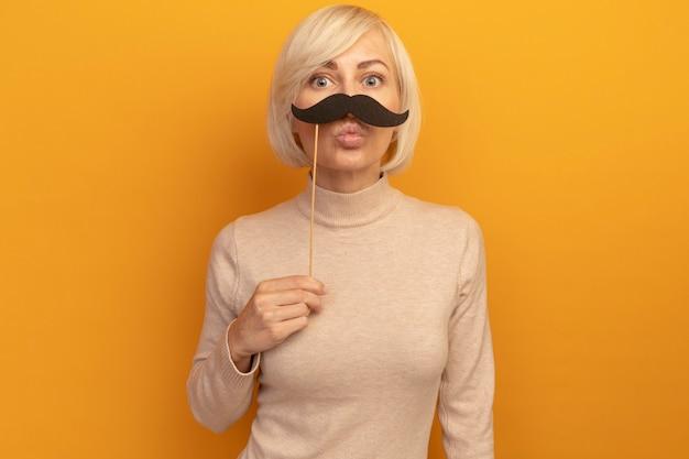 Pod wrażeniem ładna blondynka słowiańska kobieta trzyma fałszywe wąsy na patyku odizolowanym na pomarańczowej ścianie