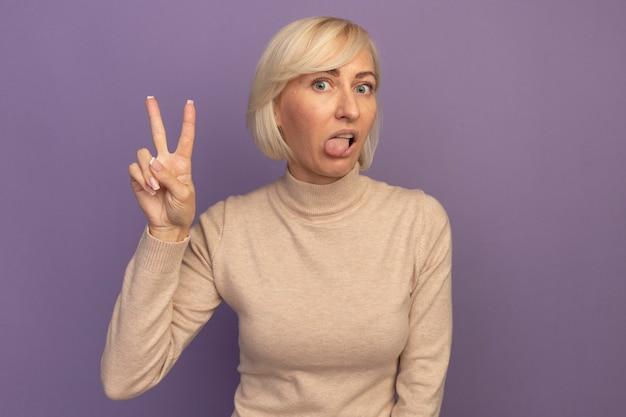 Pod wrażeniem ładna blondynka słowiańska kobieta wystawia język i gestem ręki znak zwycięstwa na fioletowo