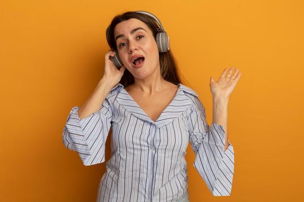 Pod wrażeniem ładna kobieta na słuchawkach stoi z podniesioną ręką na białym tle na pomarańczowej ścianie