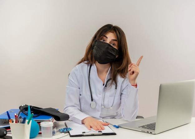 Pod wrażeniem lekarka w średnim wieku nosząca maskę medyczną siedząca przy biurku ze schowkiem na narzędzia medyczne i laptopem podnoszącym palec kładąc rękę na schowku na białym tle