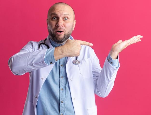 Pod wrażeniem lekarza w średnim wieku, ubranym w szatę medyczną i stetoskop pokazujący pustą rękę, wskazującą na niego odizolowaną na różowej ścianie