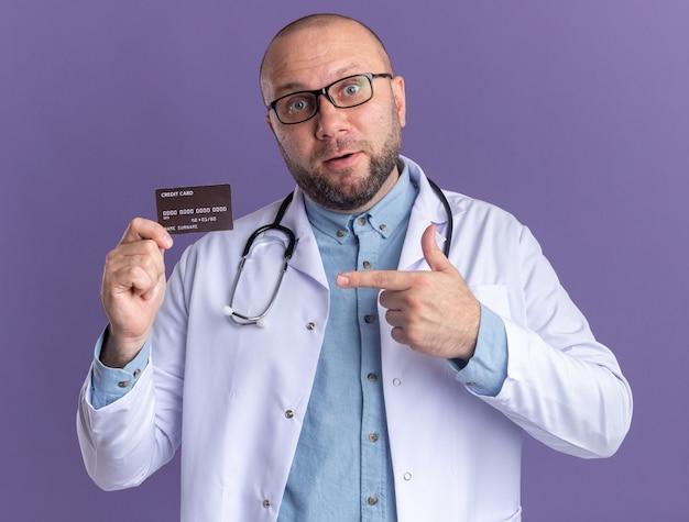 Pod wrażeniem lekarza w średnim wieku, ubranym w szatę medyczną i stetoskop w okularach trzymających i wskazujących na kartę kredytową, patrząc na przód odizolowany na fioletowej ścianie