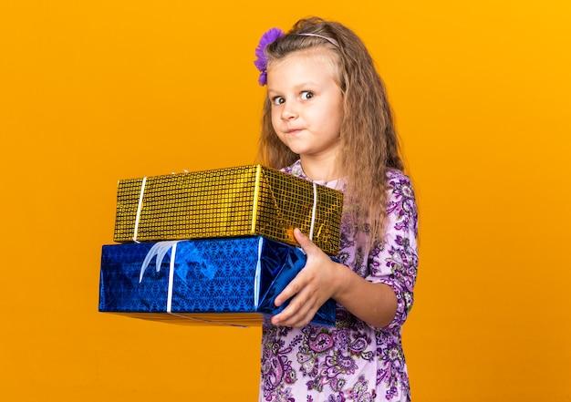 Pod wrażeniem małej blondynki trzymającej pudełka na prezenty odizolowane na pomarańczowej ścianie z miejscem na kopię