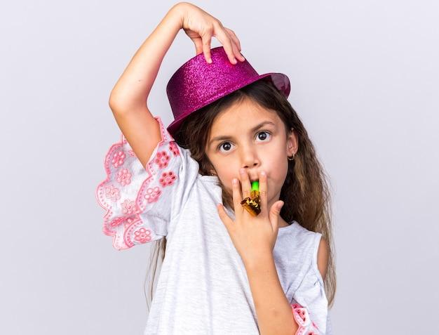 Pod wrażeniem małej kaukaskiej dziewczyny w fioletowym kapeluszu imprezowym dmuchający gwizdek imprezowy i kładący rękę na kapeluszu odizolowanym na białej ścianie z miejscem na kopię